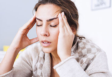 Woman sufferinf from headaches in need of acupuncture