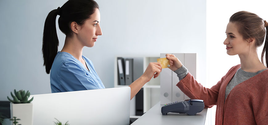 Patient paying for treatment with credit card at recption